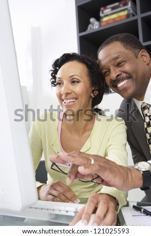 Two happy colleagues laughing in front of computer at office