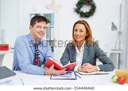 Two happy colleagues looking at camera in office