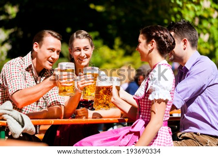 Two happy couple sitting in Bavarian Beer garden and enjoy the beer and the sun - stock photo