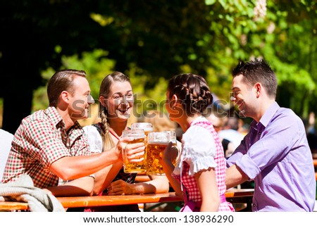 Two happy couples sitting in Bavarian Beer garden and enjoy the beer and the sun - stock photo