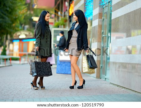 two happy elegant women shopping in the city - stock photo