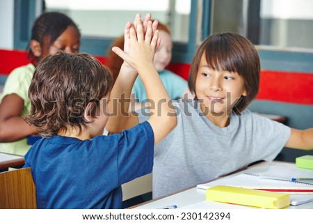 Two happy elementary school students giving high five in class - stock photo