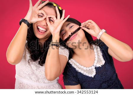 Two happy female best friends posing to camera with crazy gleeful expressions, over hot pink background - stock photo