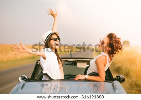 Two happy female friends enjoying road trip in their cabriolet - stock photo