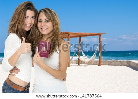 Two happy female friends holding a passport, in a beach resort - stock photo