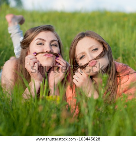 Two happy female friends playing in green grass - stock photo