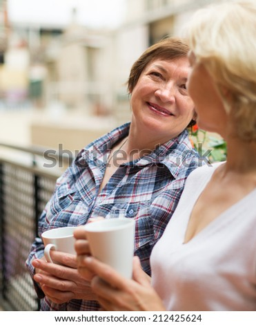 Two happy female pensioners staying on balcony with cup of tea and smiling  - stock photo