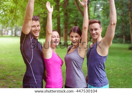 Two happy fit healthy young couple standing in a row outdoors in a green park cheering and waving with happy smiles - stock photo