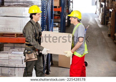 Two happy foremen carrying cardboard box at warehouse - stock photo
