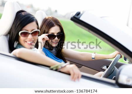 Two happy friends in the car driving everywhere and looking for freedom and fun - stock photo