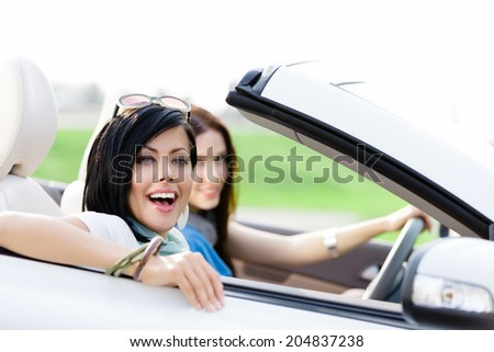 Two happy friends in the convertible car driving everywhere and looking for freedom and fun - stock photo