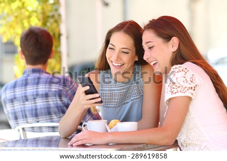 Two happy friends or sisters sharing a smart phone in a coffee shop terrace looking at device in summer - stock photo