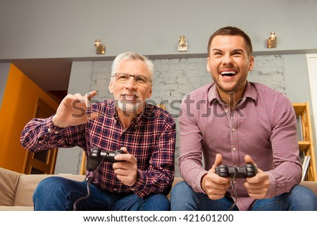 Two happy friends playing video games at home - stock photo