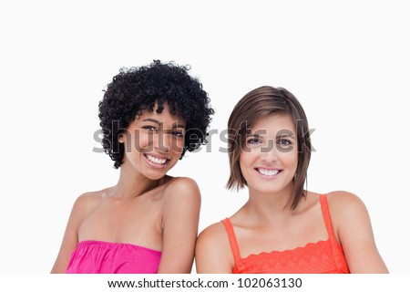 Two happy friends standing upright side by side on the white background - stock photo