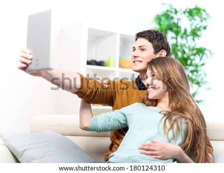 Two happy friends taking photo with tablet pc at home on the couch - stock photo