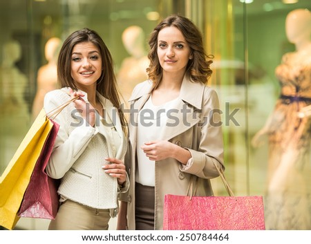 Two happy friends with shopping bag is shopping in mall and looking at the camera. - stock photo