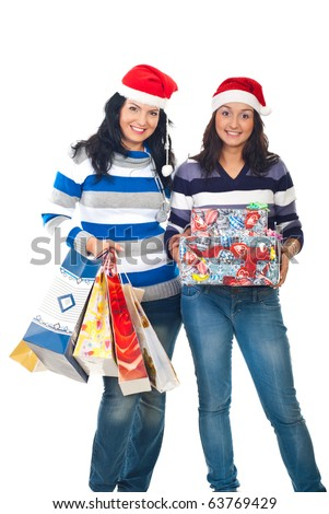 Two happy friends women holding bags and boxes  and wearing santa hats isolated on white background