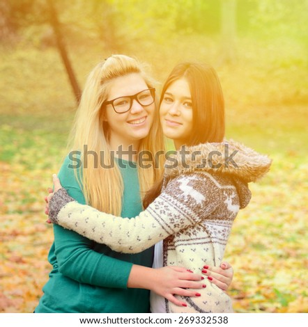 Two happy girl friends in posing in nature