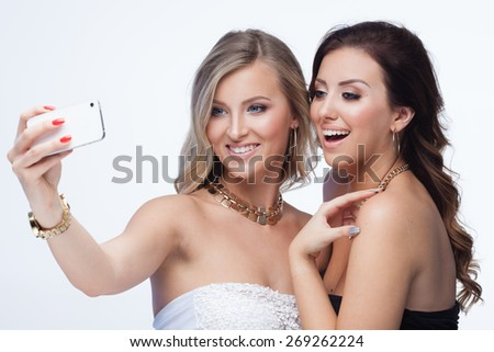 Two happy girlfriends making selfie on white background - stock photo