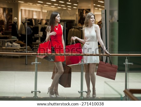 Two happy girlfriends on shopping walk on shopping centre with bags - stock photo