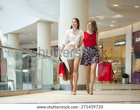 Two happy girlfriends on shopping walk on shopping mall with bags