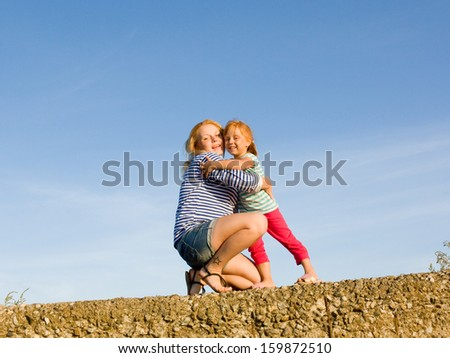 Two happy girls against the sky - stock photo