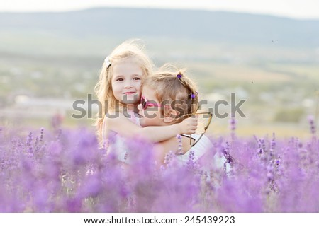 two happy girls are hugging in field