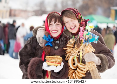 Two happy girls celebrating  Pancake Week at Russia