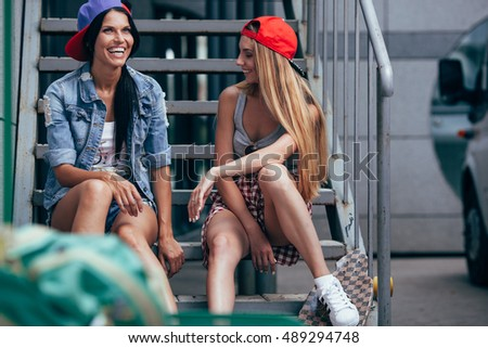 two happy girls chatting on stairs