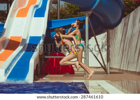 Two happy girls child jumping into swimming pool