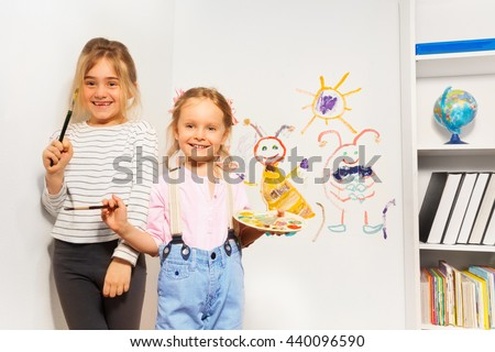Two happy girls drawing funny picture at the wall - stock photo