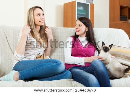 two happy girls  gossiping on sofa in home interior - stock photo