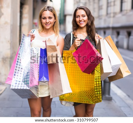 Two happy girls holding shopping bags walking at street
