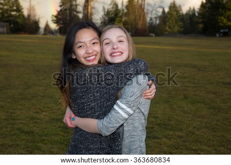 Two happy girls hugging outside