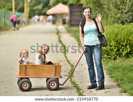 Two happy girls in a wooden wagon  - stock photo