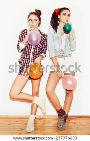 Two happy girls in knit socks and jeans shorts inflate colored balloons. White background not isolated - stock photo