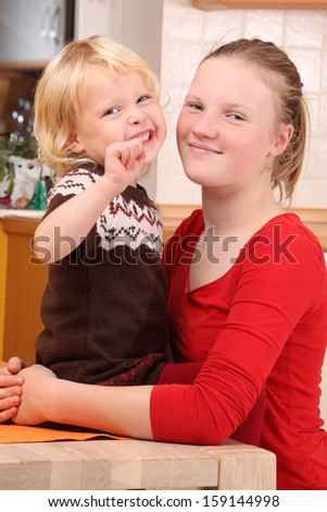 Two happy girls in the kitchen - stock photo