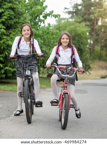 Two happy girls in uniform riding to school at morning
