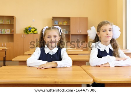 Two happy girls in uniform sit at wooden school desk in classroom at school. - stock photo