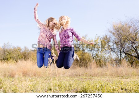 Two happy girls jumping high on empty sunny day outdoors field - stock photo