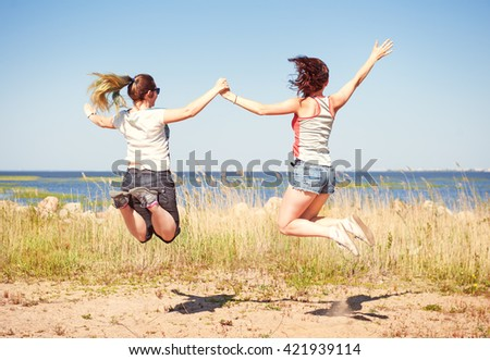 Two happy girls jumping on the beach in summer
