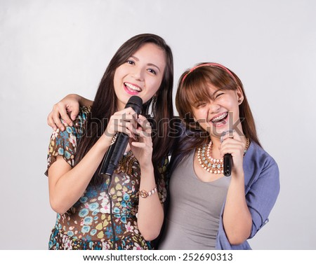 Two happy girls singing