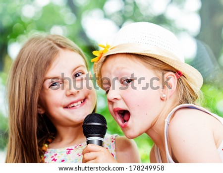 Two happy girls singing together holding microphone in hands - outdoor - stock photo