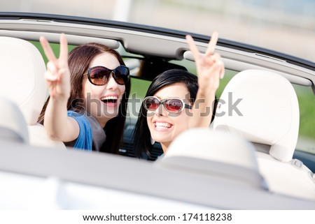 Two happy girls sitting in the car and gesturing victory sign look back and have fun while having little car trip - stock photo