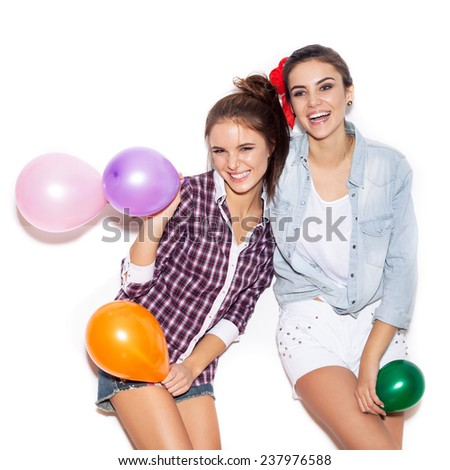 Two happy girls smiling and holding colored balloons. White background not isolated - stock photo