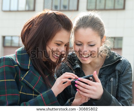 Two happy girls watch something in mobile phone - stock photo