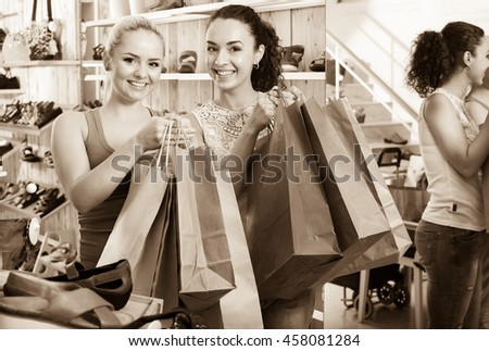 Two happy glad young women shopping shoes and looking happy with purchases. Focus on both persons. Right - the reflection in the mirror - stock photo