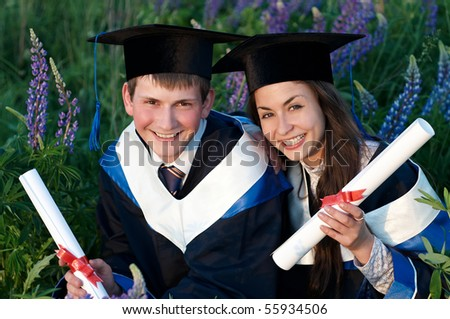 Two happy graduate students in gown and diploma sitting outdoors at sunset light - stock photo