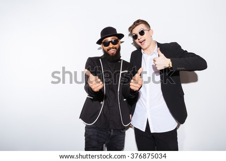 Two happy handsome young men standing and showing thumbs up over white background - stock photo