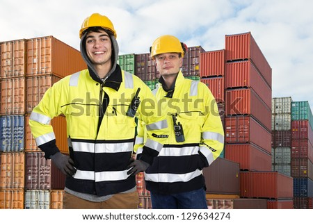 Two happy harbor workers posing in front of a huge stack of containers - stock photo